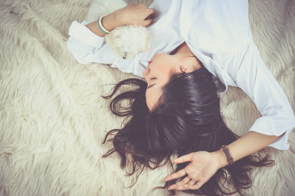 What Is Hygge? Woman having a nap with a dog