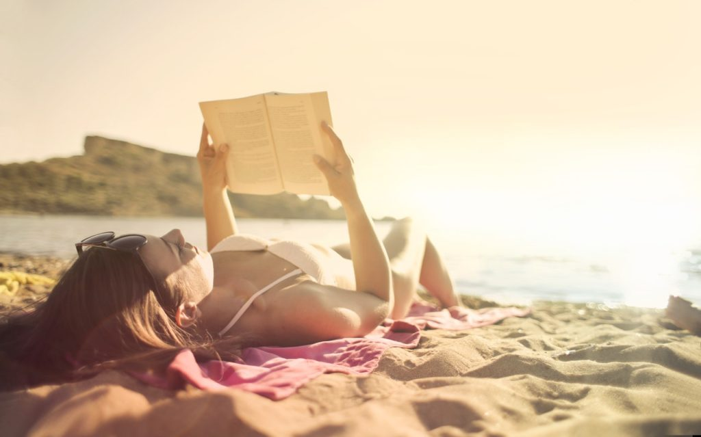 Storing bikinis lady reading on the beach